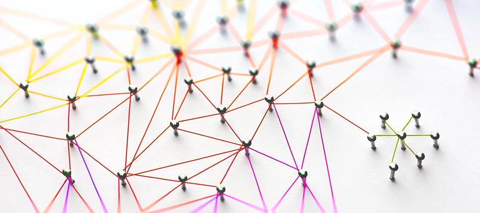Linking entities. Networking, social media, SNS, internet communication abstract. Small network connected to a larger network. Web of red, orange and yellow wires on white background.